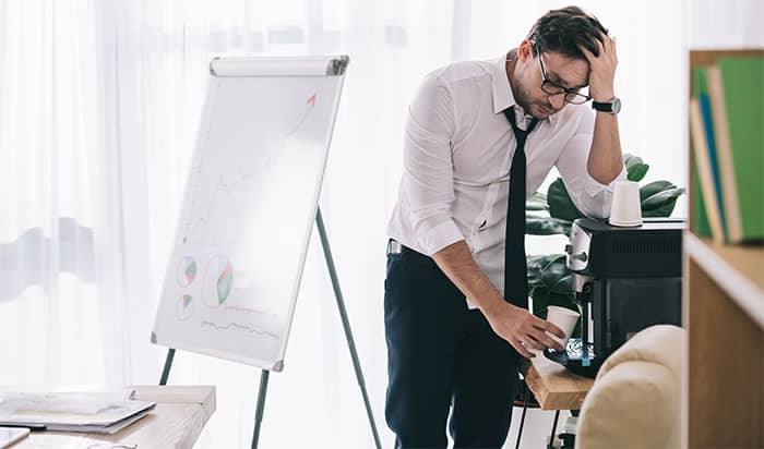 Young overworked businessman pouring coffee from office machine