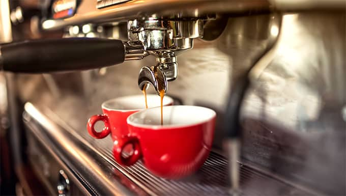 Coffee machine preparing fresh coffee and pouring into red cups at restaurant, bar or pub